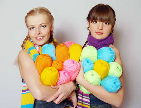 Portrait of two beautiful girls with colorful yarn photo