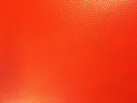 Bright orange leather background closeup.