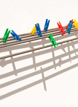 colored clothespins against a white wall with shadows, vertical orientation, closeup