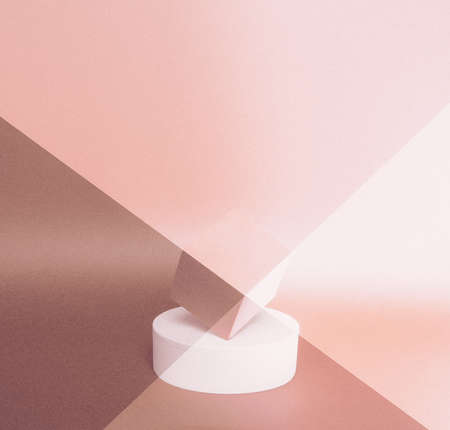 Bright balance of 2 pedestals (cube and round) on a paper background. In pastel pink, with gradient, grain and diagonally toned. Advertising place. Blank product stand with light.