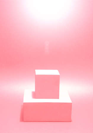 Photo of a bright podium (pedestal) of two cubes on a paper background. In pink, with gradient and glare. Advertising place. Blank product stand and abstract background with light. 스톡 콘텐츠