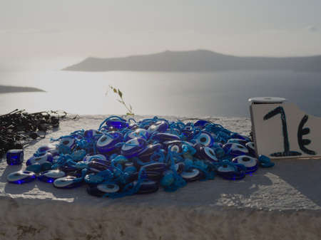 A handful of amulets Nazar are laid out on a stone fence for sale for 1 euro against a sea landscape with sunset light. An island is visible in the distance.