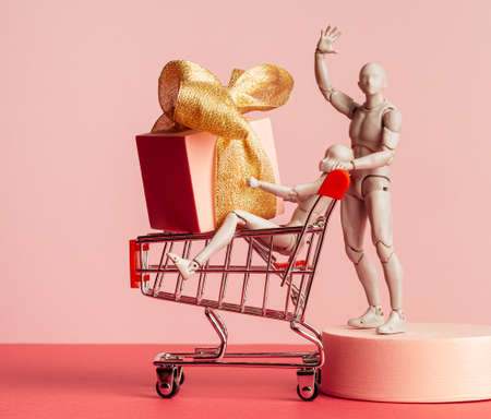 a male mannequin with a supermarket trolley in which a female dummy sits and holds a large box tied with a gold ribbon. The background is pink. 版權商用圖片