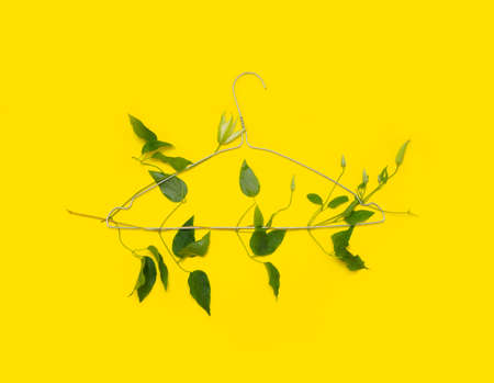 one iron clothes hanger braided with liana on a yellow background