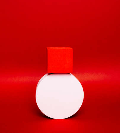 Bright balance of 2 pedestals (red cube and white round) on a paper background. In saturated red, with gradient and grain. Advertising place. Blank product stand and abstract background with light. 版權商用圖片 - 157870242