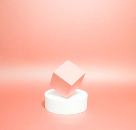 Bright balance of 2 pedestals (cube and round) on a paper background. In peach, with gradient. Advertising place. Blank product stand and abstract background with light. 版權商用圖片