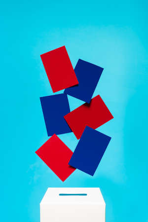 election concept - blue and red cards fall into a white voting box with a slot, the background is blue, levitation Zdjęcie Seryjne