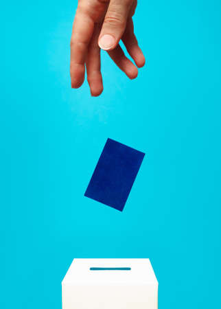 election concept - a woman's hand puts a blue card into a white voting box with a slot, the background is blue, levitation 免版税图像