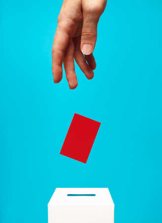 election concept - a woman's hand puts a red card into a white voting box with a slot, the background is blue, levitation