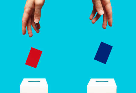 election concept - two a woman's hands puts a blue and red cards into a white voting box with a slot, the background is blue, levitation Banque d'images