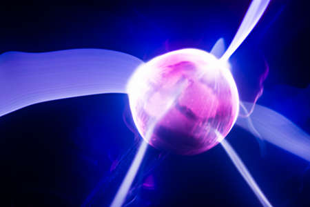 abstract glowing ball of pink color with rays emanating from it in blue space, defocused lights