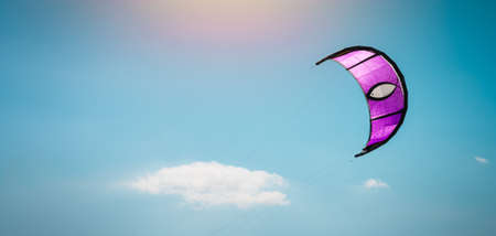 pink kite on a background of blue sky, sun and clouds, banner