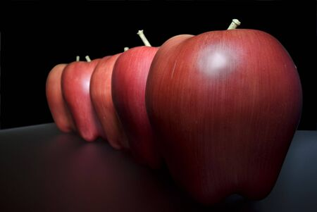 taffy apple: red plastic apples over mirror and selective focus Stock Photo