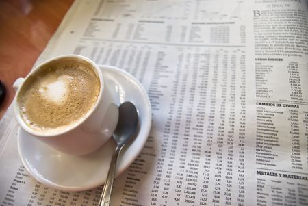 exceeds: Cup of coffee, spoon and newspapers