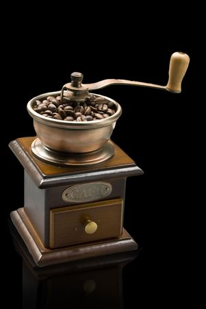 colombian food: Old-fashioned coffee grinder with coffee beans  isolated over black Stock Photo