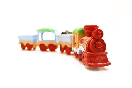 Front view of a  toy train. The focus is on the front of the engine. isolated on white.