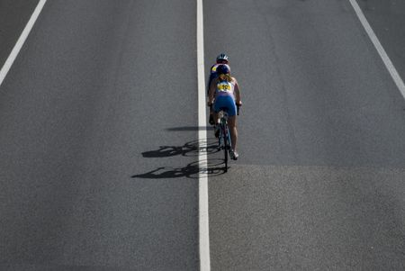Couple of girls cycling along road, taking part in a competition  Stock Photo
