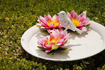 Plastic lotus flowers and decoration bird on a dish on a green plastic lotus flowers and decoration bird on a dish on a green grass background stock photo mightylinksfo