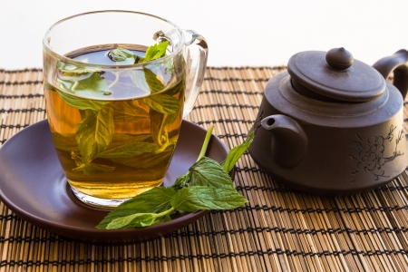 Green tea and leaves of mint in a glass cup on a bamboo mat with a clay pot photo