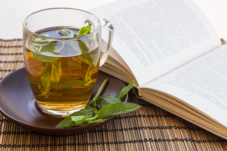Green tea and leaves of mint in a glass cup on a bamboo mat with an open book photo