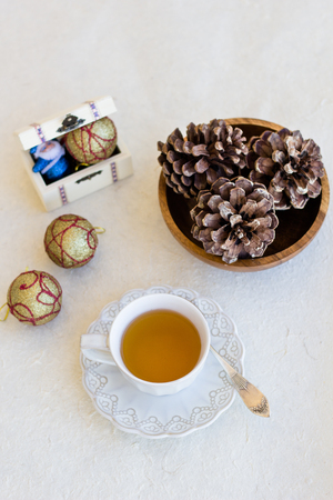 Christmas composition with cup of tea, balls and bumps on a white cloth photo