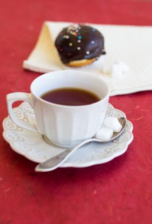 A cup of tea with fresh chocolate sufgniya (donut) photo