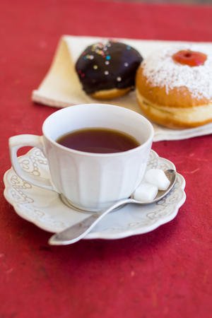 A cup of tea with fresh chocolate sufgniyot (donuts) photo