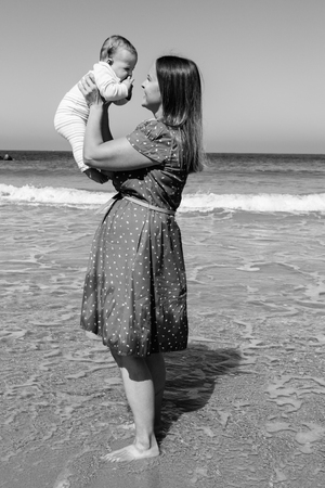 Mother playing with cute little daughter on the beach photo