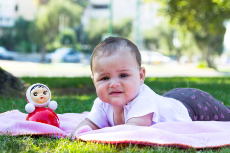 Little baby girl playing on the grass photo