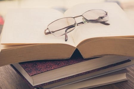 cramming: Pile of books and eyeglasses on a wooden table, retro effect