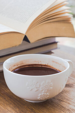 books on a wooden surface: Cup of hot chocolate on a wooden surface with books Stock Photo