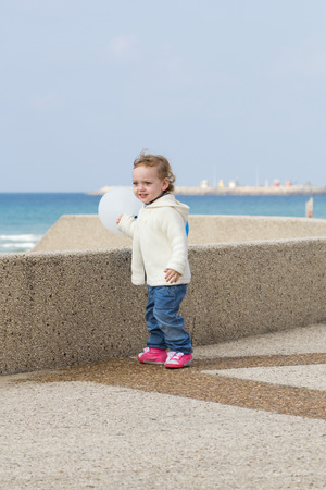 Cute little girl playing on a winter beach photo