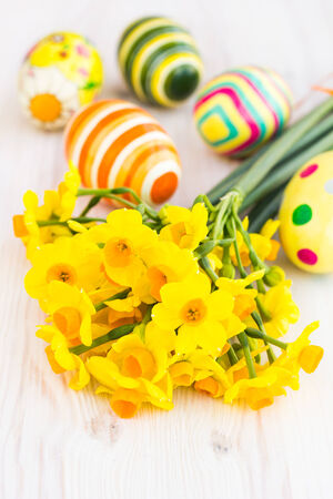 Yellow daffodils with easter eggs , selective focus photo