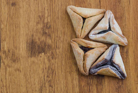 haman: Hamantaschen cookies for Purim on a wooden table