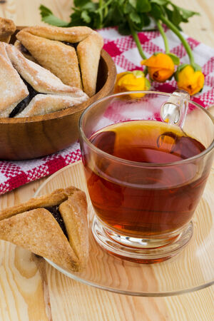 Hamantaschen cookies for Purim with cup of tea on a wooden table photo