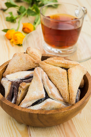 hamantaschen: Hamantaschen cookies for Purim with cup of tea on a wooden table