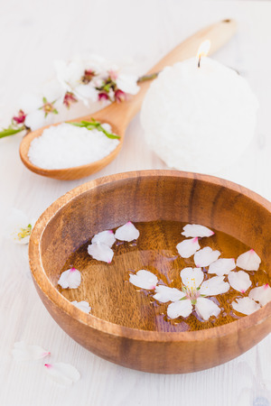 Wooden cup with petals for hands spa, selective focus photo