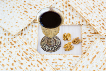 kiddush: Silver kiddush wine cup  for passover with matzot, selective focus