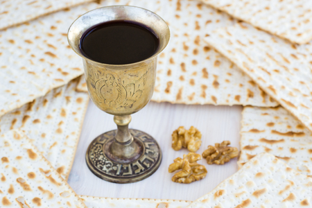 matzot: Silver kiddush wine cup  for passover with matzot, selective focus