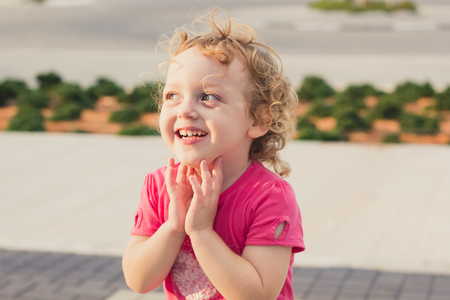 Cute baby girl with curly hair having fun at a park photo