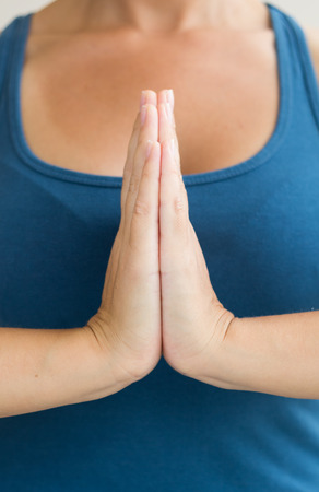 Hands in Namaste prayer mudra by practicing woman, selective focus
