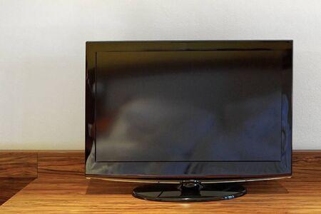 tv set: Black lcd TV set at wooden shelf