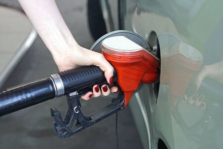 petrol station: Woman filling car with gas at petrol station