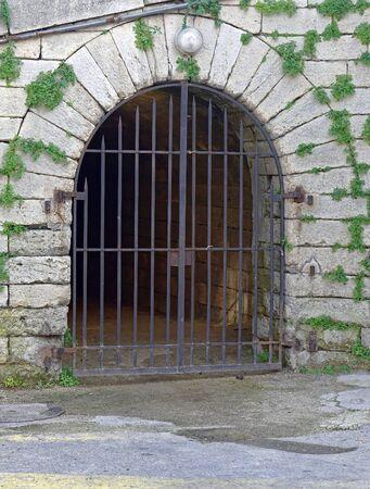 rejas de hierro: puerta de arco de piedra con barras de hierro de la puerta Foto de archivo