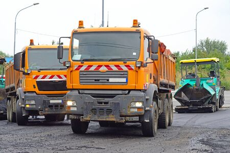 Road works trucks with asphalt and surfacing machine Stock Photo