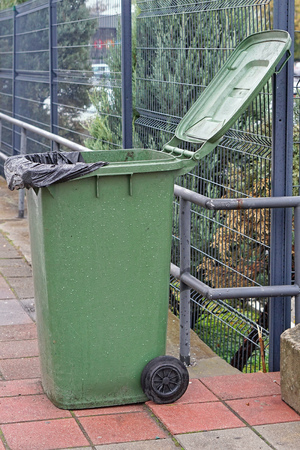 Open green wheelie bin with garbage bag