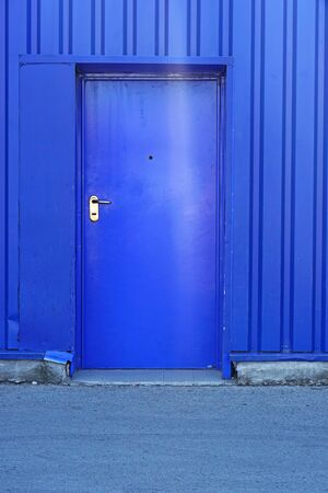 Blue door at industrial building exterior Stock Photo