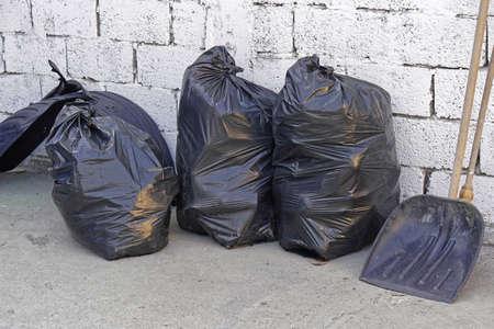 Three big blacks trash bags in front of wall