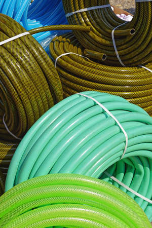 Many new green garden hoses in coils
