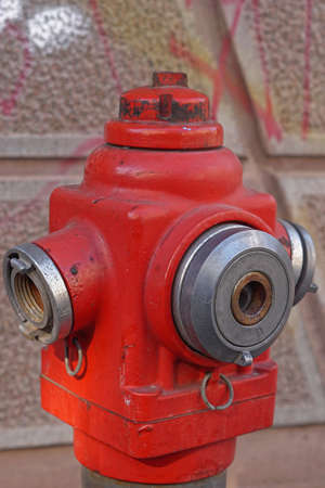 Red fire hydrant with water valve close up